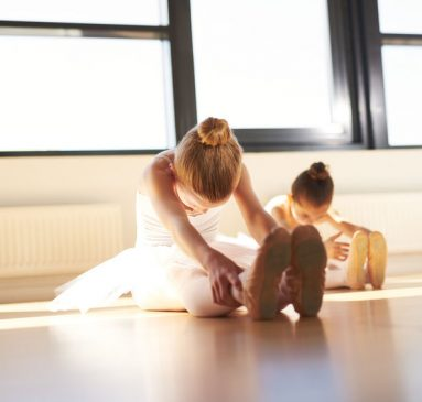 Two Young Ballerinas Doing an Exercise, Especially for their Legs, Inside the Studio Before the Actual Dance Rehearsal.
